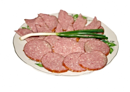 Sliced salami on a plate with fresh green onion  Stock Photo