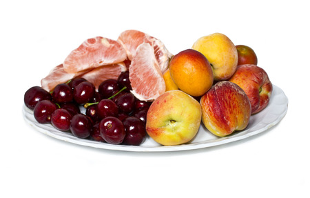 A plate with cherry, grapefruit and apricot fruits   Stock Photo