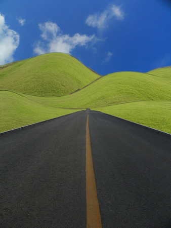 uphill: Empty road with green hills and blue sky.