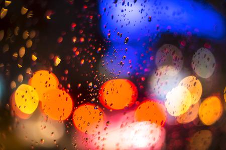 kropla deszczu: Krople deszczu na oknie w nocy z bokeh światła tła Publikacyjne