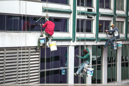 window repair: group of workers cleaning windows service on high rise building Editorial