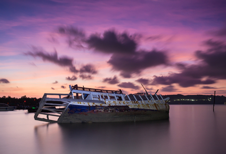 sunken boat: The broken ship along with the sea and sunset twilight sky