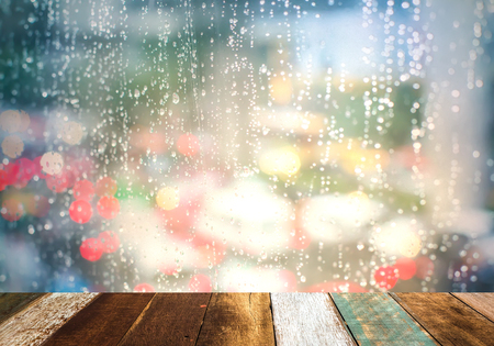 de focus: Drops Of Rain On Blue Glass Background. Street Bokeh Lights Out Of Focus. Autumn Abstract Backdrop Stock Photo