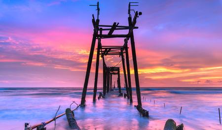 orange sunset: Broken wood bridge and waves crashing on sea at during sunset Stock Photo
