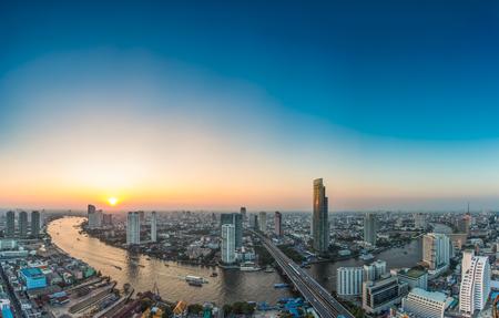バンコク (タイ) 川に沿って現代ビジネス建物夕暮れ時に輸送