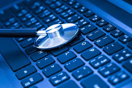 ブルーのトーンのコンピューターまたはデータ分析 - コンピューターのキーボード上の聴診器