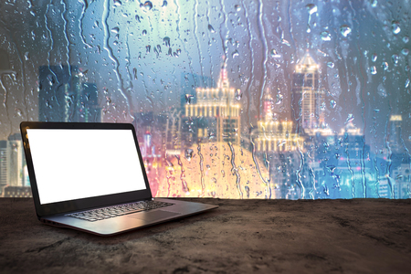 Laptop on building high angle background city on rainy days.