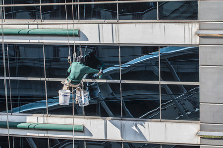 window reflection: group of workers cleaning windows service on high rise building Stock Photo