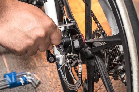 serviceman: Mechanic serviceman repairman installing assembling or adjusting bicycle gear on wheel in workshop Stock Photo