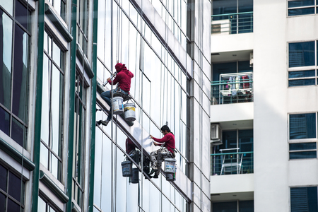 window reflection: group of workers cleaning windows service on high rise building Editorial