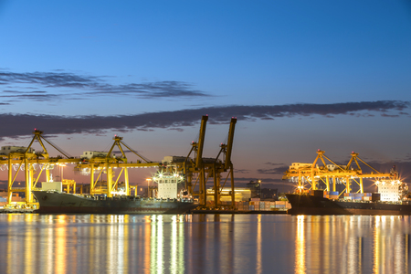 good night: Container ship in the harbor of Hamburg, night shot. Cloudy sky. Stock Photo
