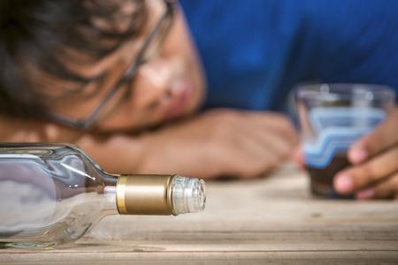 borracho: Hombre latino borracho y solitario que sostiene una botella de ron o whisky