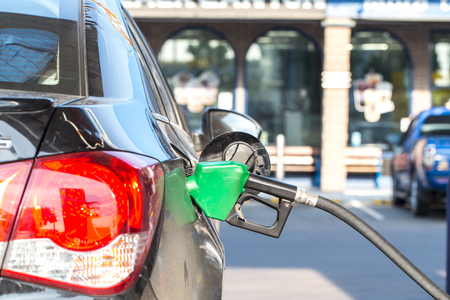 fillup: grey car at gas station being filled with fuel Stock Photo