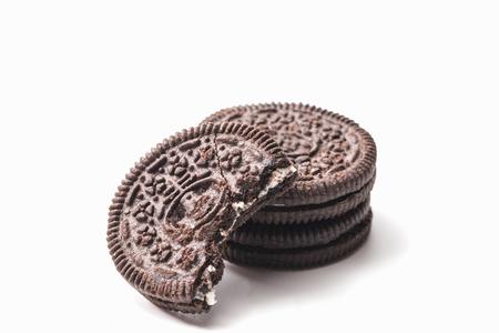 chocolate cookie: Una mordedura en la galleta de chocolate y crema aislados en blanco
