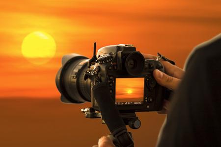 太陽を撮影するカメラマン