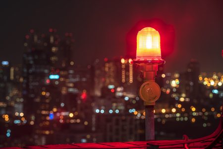 obstruction: twin red obstruction lights on the rooftop with city view in the background Stock Photo