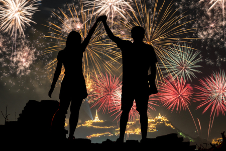 children celebration: Happy Couple Standing On the hill watching fireworks