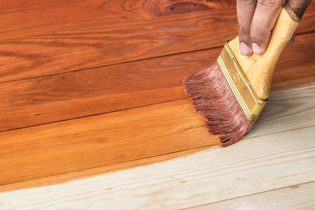 brocha de pintura: mano que sostiene un cepillo de aplicación de pintura barniz sobre una superficie de madera Foto de archivo