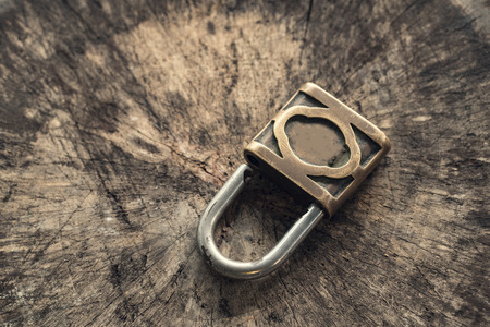 circumspect: Old lock on wood background