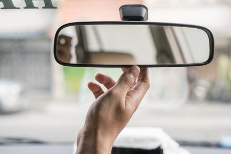 mirror: Hand adjusting rear view mirror.