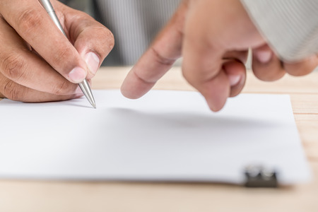 The employer shows that the employee will be written and signed. Stock Photo