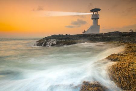 dramatics: Seascape at sunset. Lighthouse on the coast Stock Photo