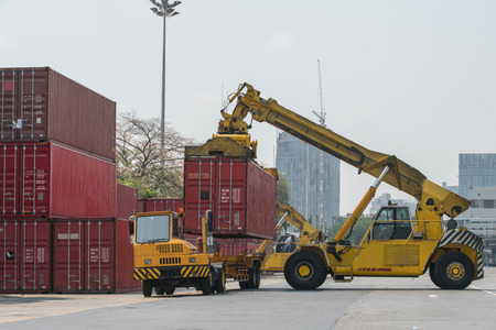 flatbed truck: forklift handling container box loading to freight train
