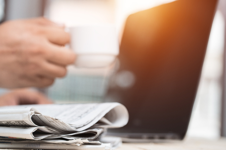Cup of  Newspaper on the desk businessman.
