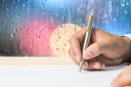 clipped: Hand of businessman in suit filling and signing with silver pen partnership agreement form clipped to pad closeup. Business success, contract, paperwork or lawyer concept Stock Photo