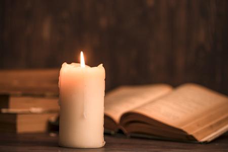 教育コンセプトです。昔の木製の背景にぼろぼろの古い本のキャンドルを燃焼をクローズ アップ。ろうそくに焦点を当てる