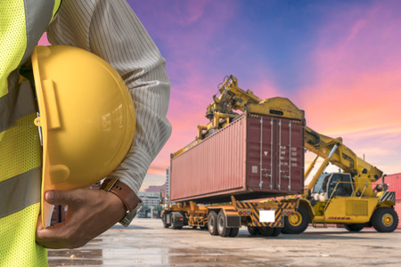 engineer in suite holding helmet with blur logistic background Reklamní fotografie