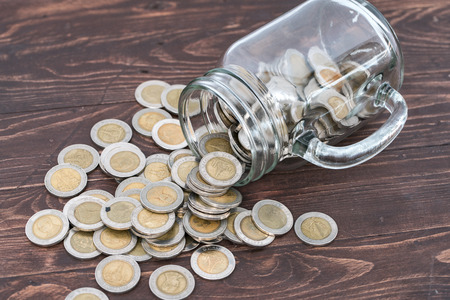 money jar: Coins in money jar on wooden background