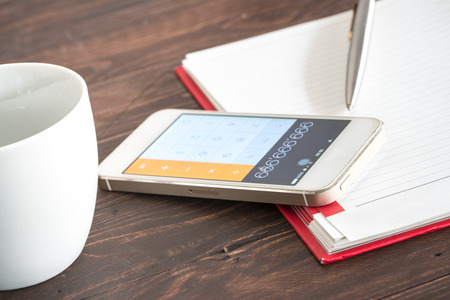 cost estimate: Notebook with pencil and smartphone as a calculator. Stock Photo