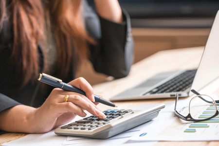 credit report: Close up of female accountant or banker making calculations. Savings, finances and economy concept
