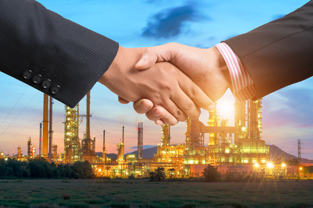 industry background: Business handshake with refinery plant at night background Stock Photo