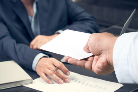 Hand of a businessman hands over a resignation letter on a wooden table