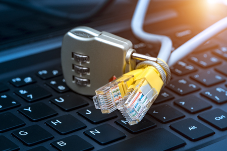 Lock and network cable with computer keyboard background. The concept of computer security Stock Photo
