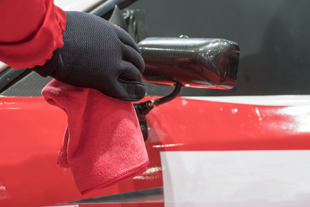 valeting: A man cleaning car with microfiber cloth, car detailing (or valeting) concept