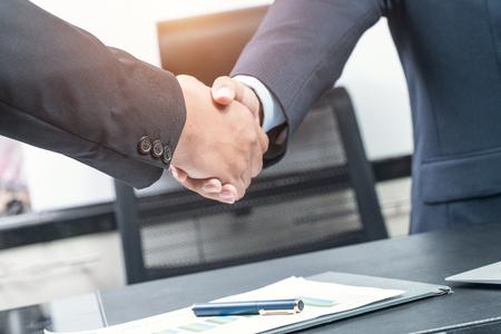 buen trato: Buen negocio. Primer plano de dos personas de negocios apretón de manos mientras está sentado en el lugar de trabajo Foto de archivo