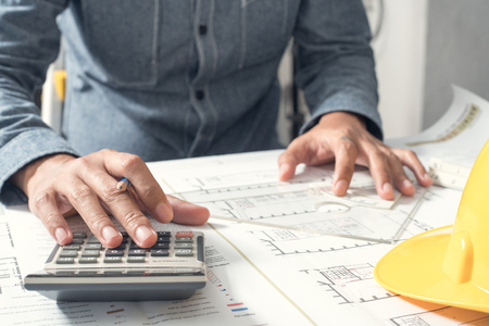 calculated: Close up of the hands of architect is calculated using the calculator.