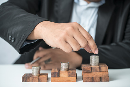 thrifty: picture of man putting stack of coins into one row Stock Photo