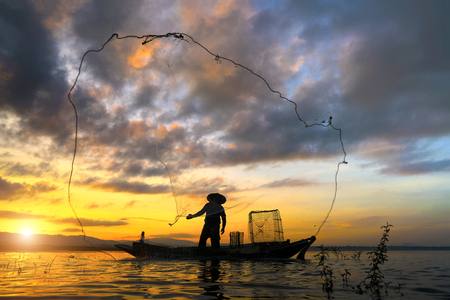 avocation: Silhouette of traditional fishermen throwing net fishing lake at sunrise time.(The casting people living along the River) Stock Photo