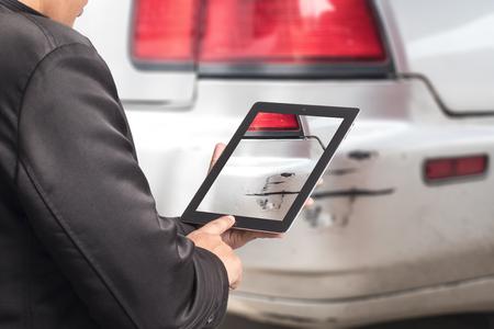事故保険の損害で彼の車を撮影する男