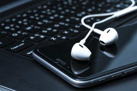 Smartphone and earphones on table. Focus on earphones.