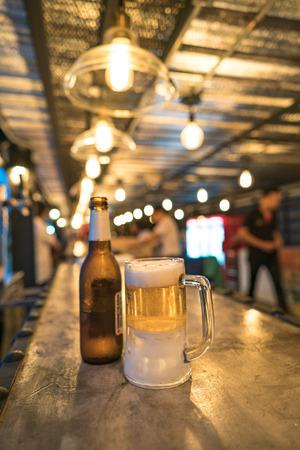 unbottled: Glass of light beer on a dark pub.