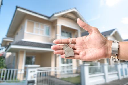新しい家の前で家の形をしたキーホルダーに家の鍵を保持しています。 写真素材
