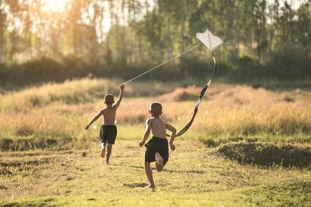 自然の中の夏の牧草地で実行するカイトと幸せな子供女の子