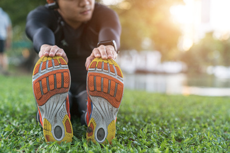 Attractive fit young man stretching before exercise, sunrise early morning backlit. Shallow depth of field, focus on shoes Stock Photo