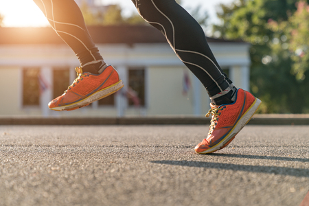 close up of urban runners legs run on the street with copy space