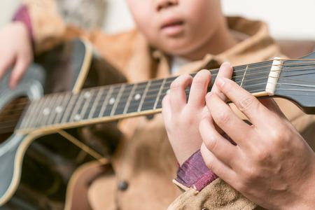 Leraar geeft gitaarlessen op leerling in een klaslokaal